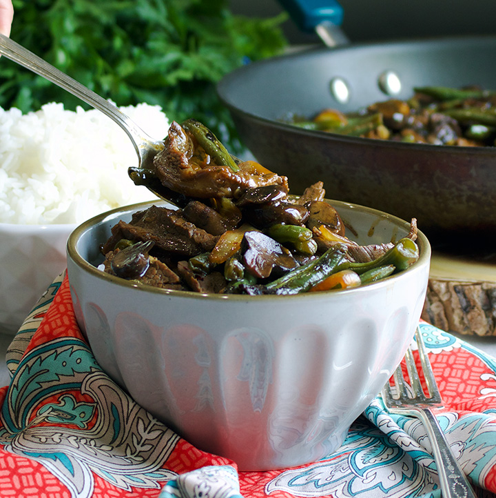 Spooning beef and vegetable stir fry over rice.