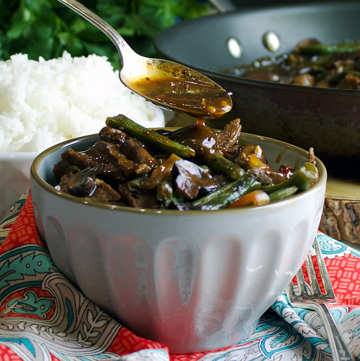 Drizzling stir fry sauce over beef stir fry with green beans and mushrooms