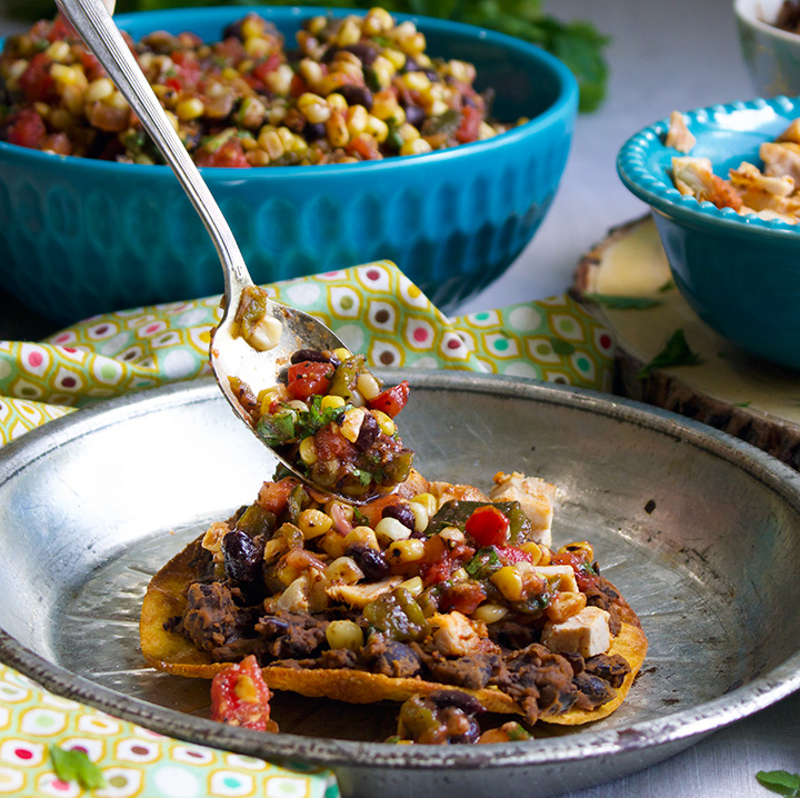 Topping a black bean tostada with corn salsa