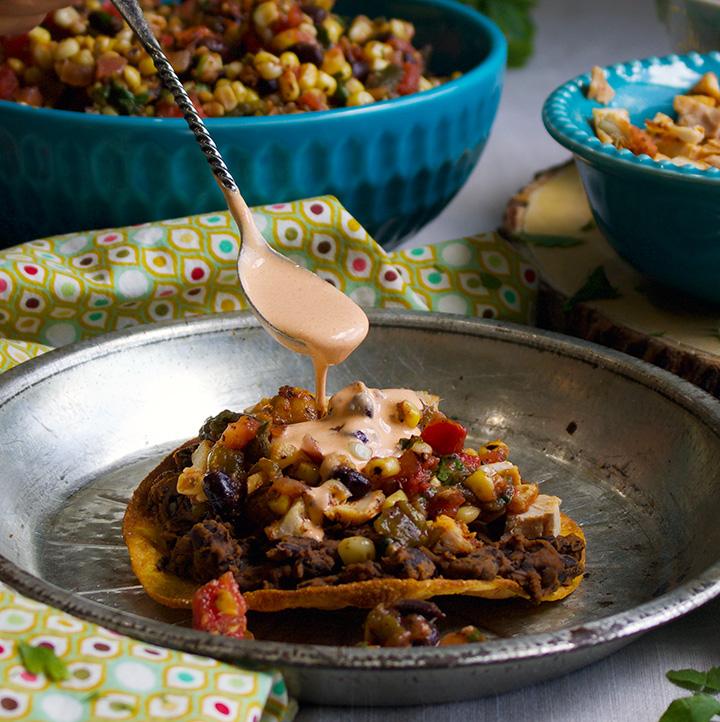 Pouring enchilada cream over a black bean tostada with corn salsa.