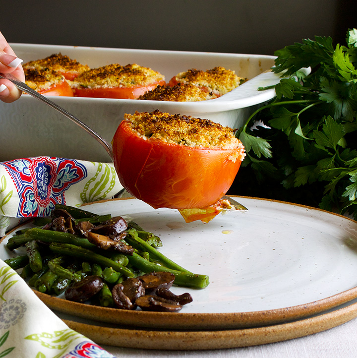 Putting a cheesy stuffed tomato onto a plate with balsamic glazed vegetables