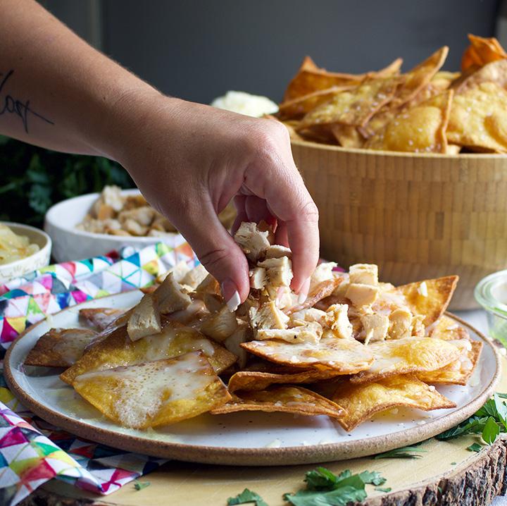 Putting chili chicken on nachos