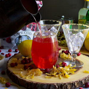 Pouring cranberry green chili lemonade into glasses