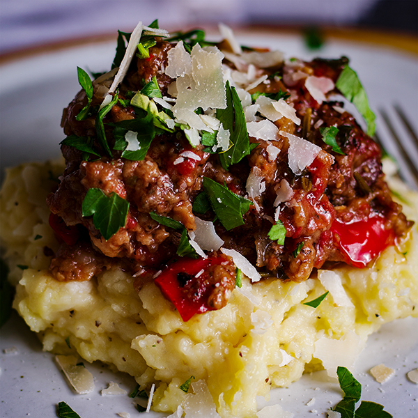 A plate of Tuscan Braised Beef over Garlic Mascarpone Mashed Potatoes.