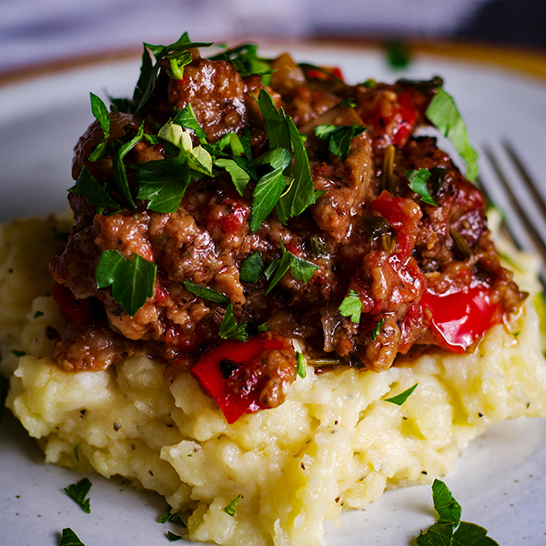 A plate of garlic mascarpone mashed potatoes topped with Tuscan Braised Beef and fresh parsley.