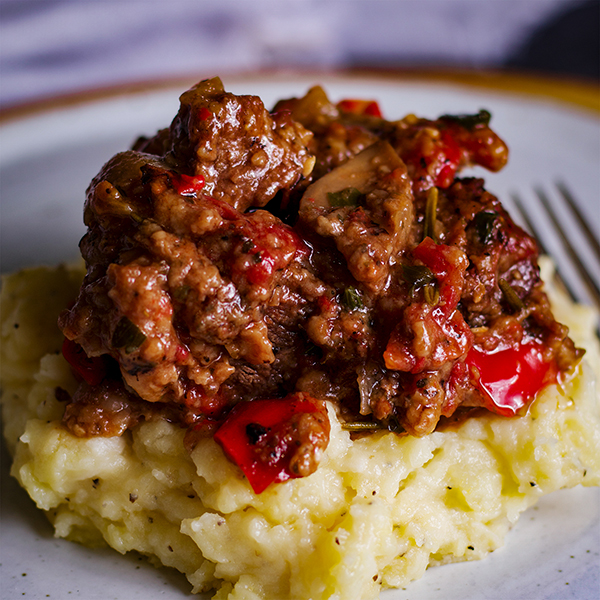 A plate of garlic mascarpone mashed potatoes topped with Tuscan Braised Beef.