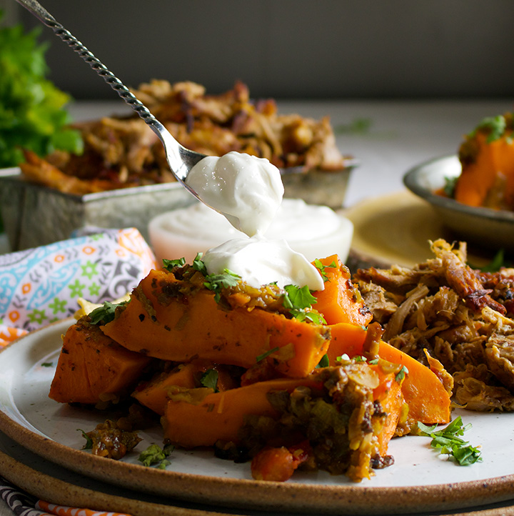 Topping Chili Roasted Sweet Potatoes with sour cream.
