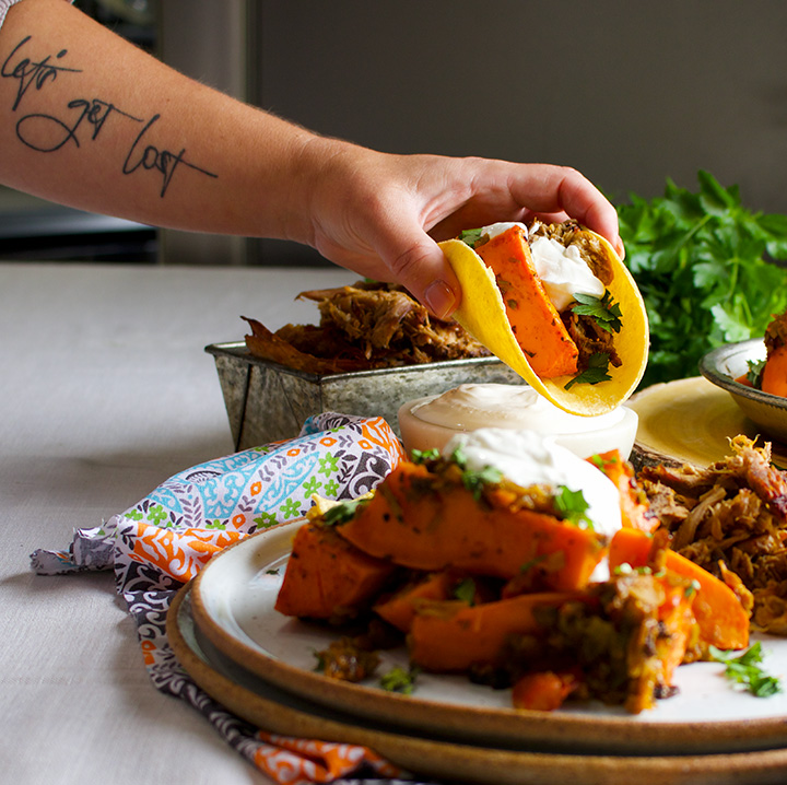 A taco made with Chili Roasted Sweet Potatoes and Carnitas