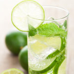 A cuban mojito with lime slices and mint.