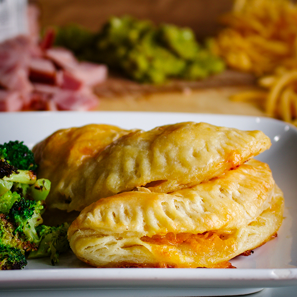 Two ham and cheese hand pies on a plate.