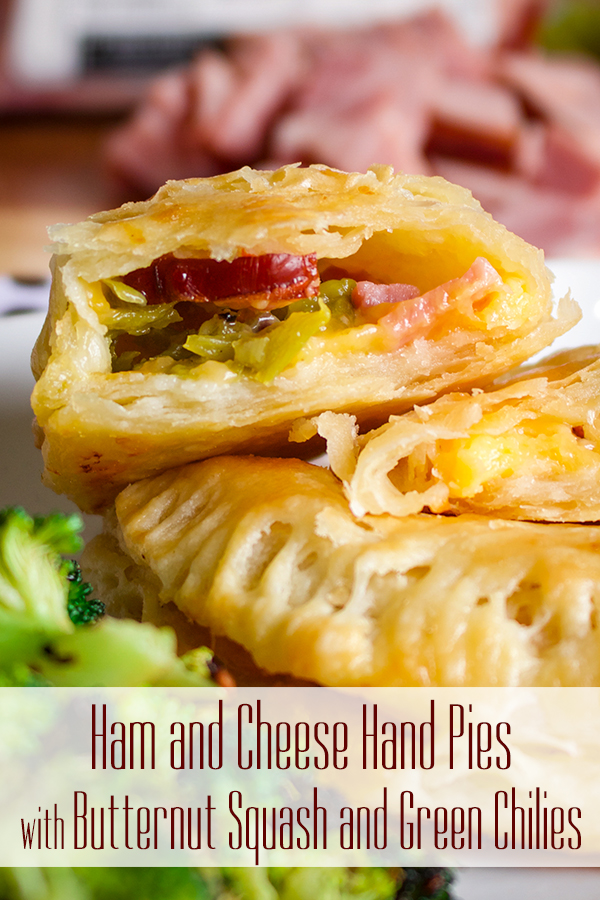 Two ham and cheese hand pies on a plate, one broken open to see the filling.