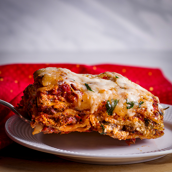 Serving a slice of the best homemade lasagna with sausage and cheese.