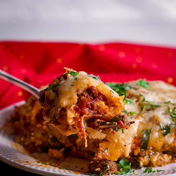 Taking a bite of classic homemade lasagna with Italian sausage.