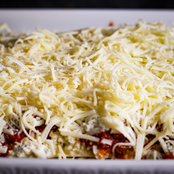 Topping a pan of homemade lasagna with a lot of cheese.