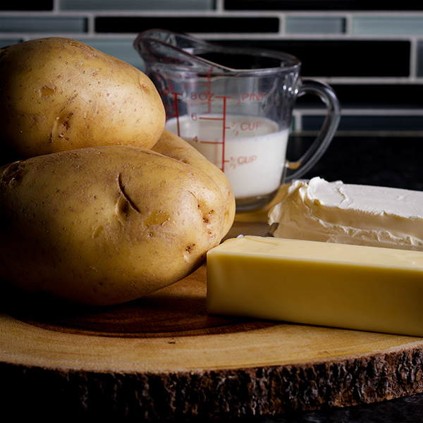 The ingredients for cream cheese mashed potatoes: Yukon gold potatoes, milk, cream cheese, and butter.