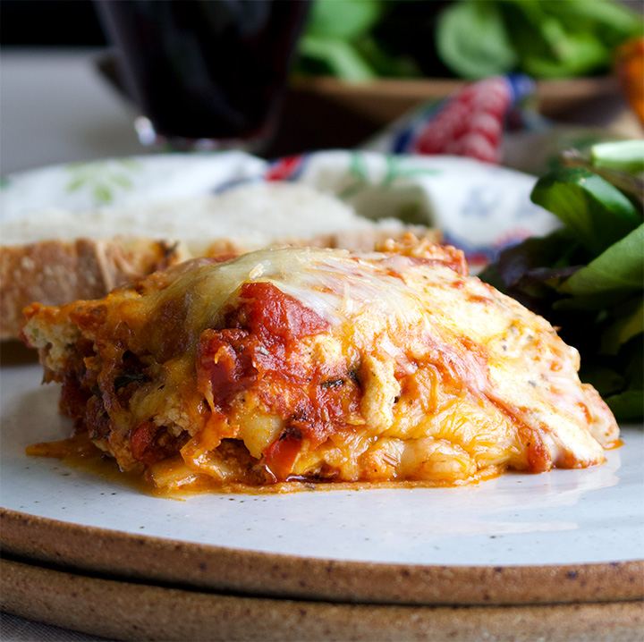 Classic homemade lasagna, warm from the oven, on a plate, ready to eat.
