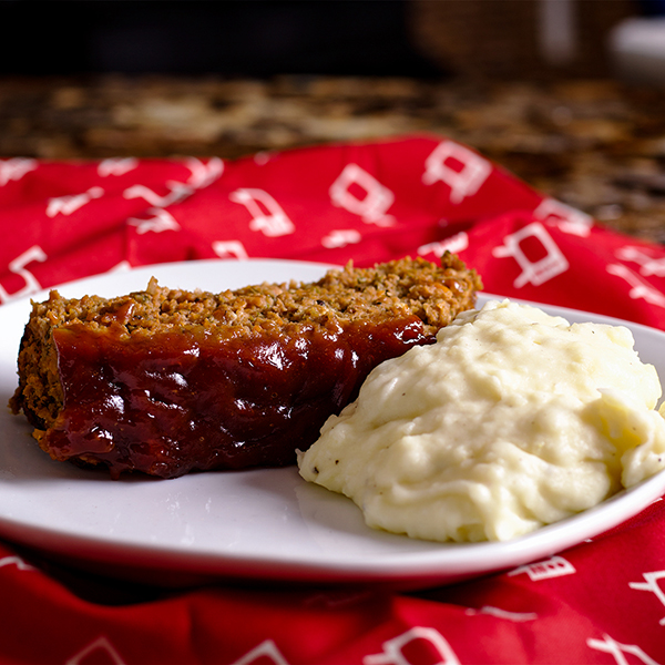 A slice of classic American meatloaf with sausage on a plate with mashed potatoes.
