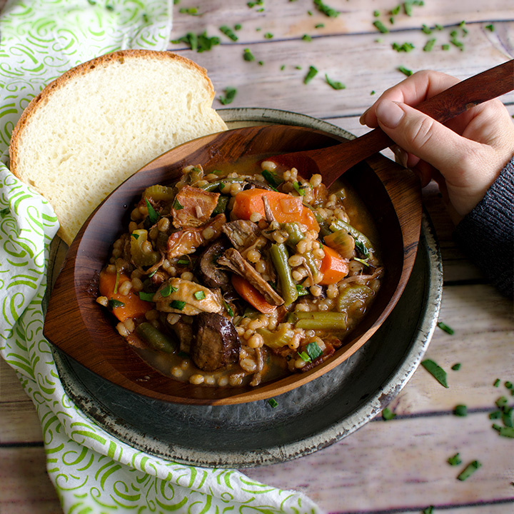Getting ready to eat a a bowl of beef and barley soup with a slice of homemade bread.