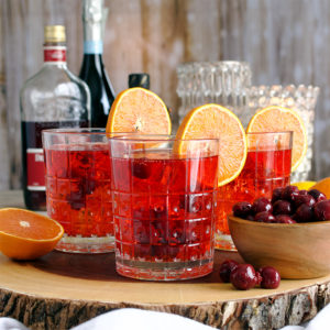 A tray with three glasses of Cherry Citrus Prosecco Spritz cocktails.