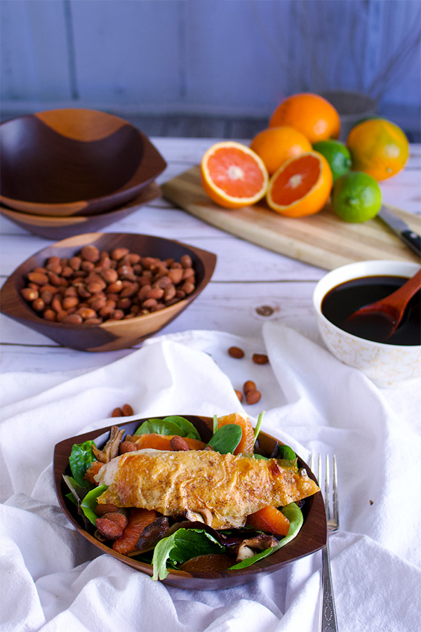 A bowl of roasted shiitake salad with oranges and citrus ponzu with roast chicken