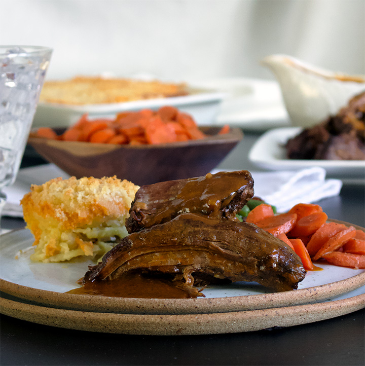 Slow Cooker Tri-Tip steak smothered in fennel and coriander gravy, on a plate with potato gratin, glazed carrots, and green beans.