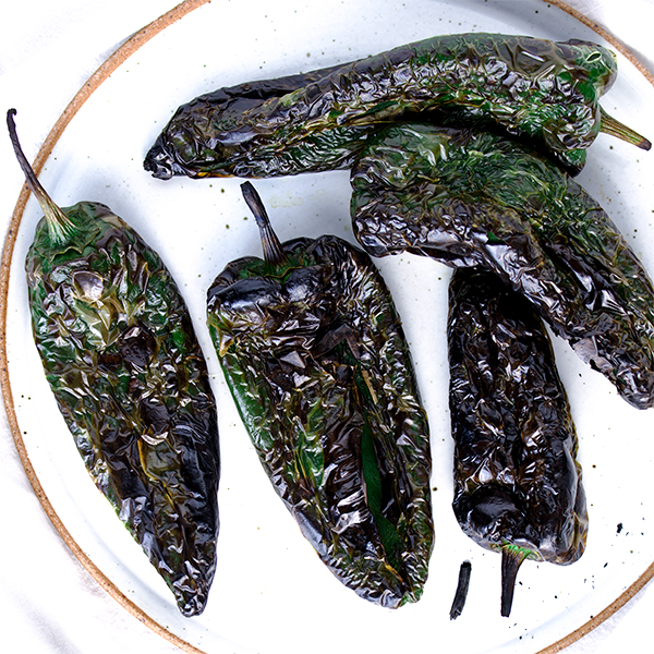 A plate with 5 roasted poblano peppers.