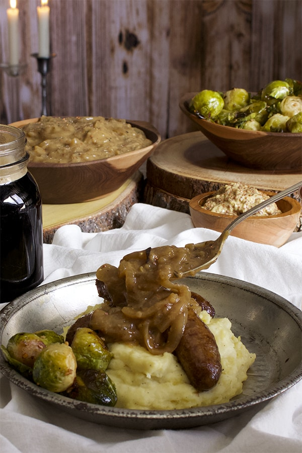 Spooning onion gravy over Guinness cooked bangers and mash