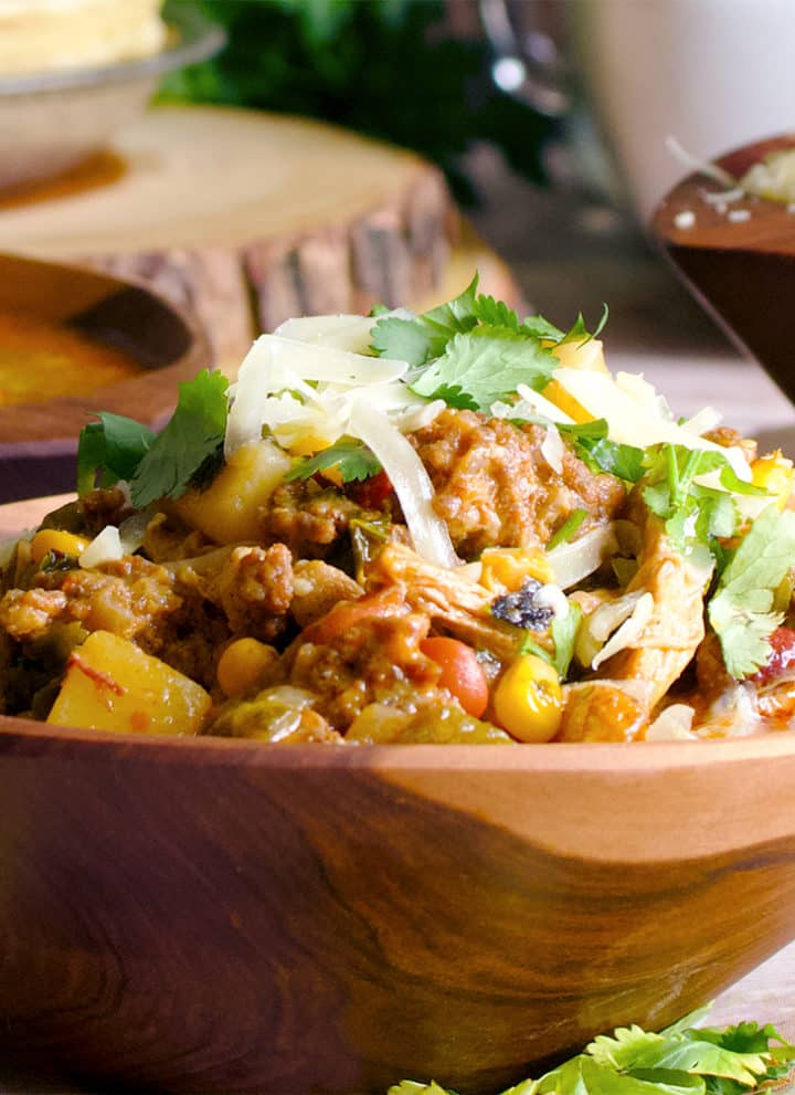 A bowl of creamy chicken chili with roasted corn, chorizo, and cheese.