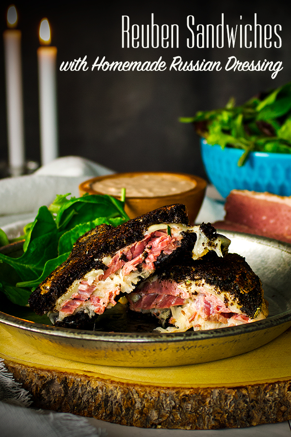 A plate with two halves of a Reuben Sandwich and salad on it.