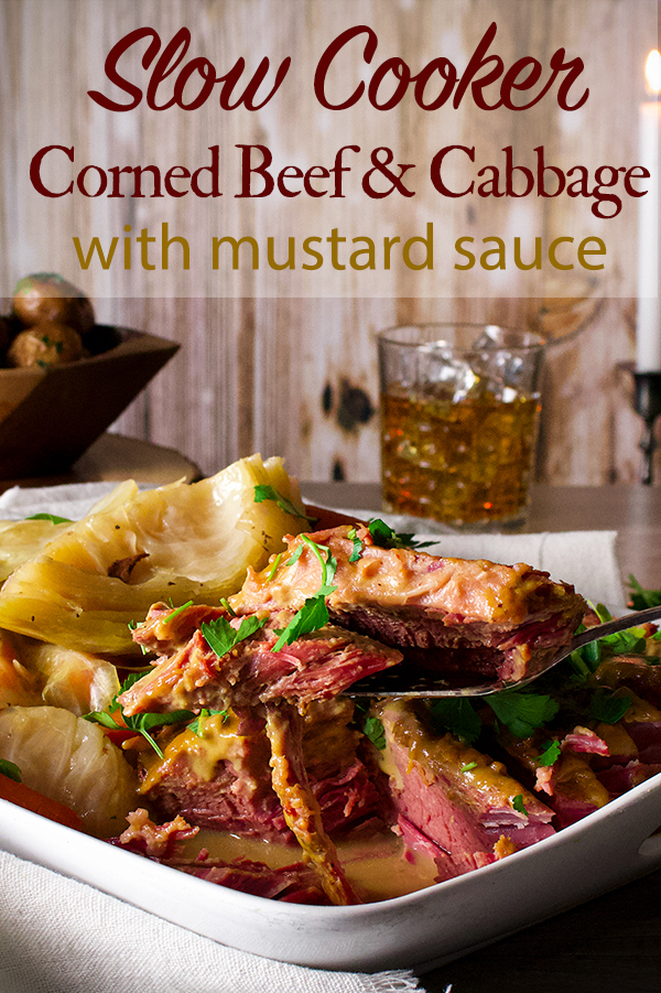 A platter on a table with corned beef and cabbage with mustard sauce and parsley buttered potatoes.