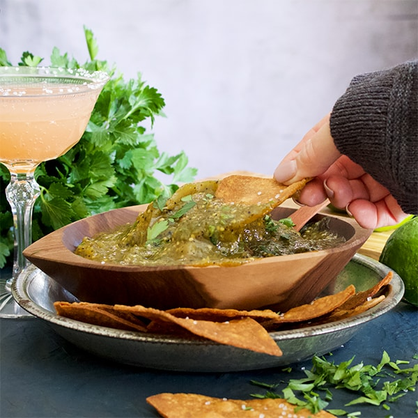 Dipping a tortilla chip in a bowl of salsa verde (roasted tomatillo sauce)