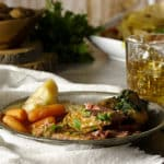 A plate of corned beef and cabbage with carrots and parsley buttered potatoes.