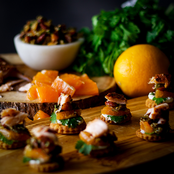 A tray of Orange Cedar Roasted Salmon Appetizers on a Cheddar Cracker with Almond Chili Salsa