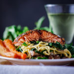 A plate of miso buttered noodles with salmon and vegetables.