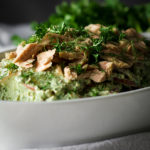 A bowl of potato salad with creamy avocado and herb green sauce and tuna fillets.