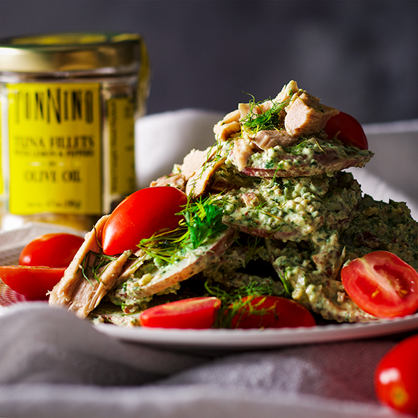 A plate of potato salad with creamy avocado and herb green sauce, tuna fillets and tomatoes