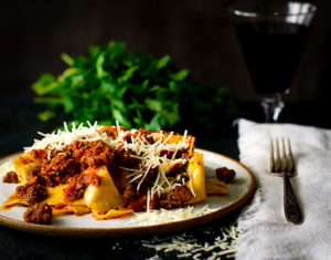 A plate of pasta bolognese with pappardelle pasta and parmesan cheese.