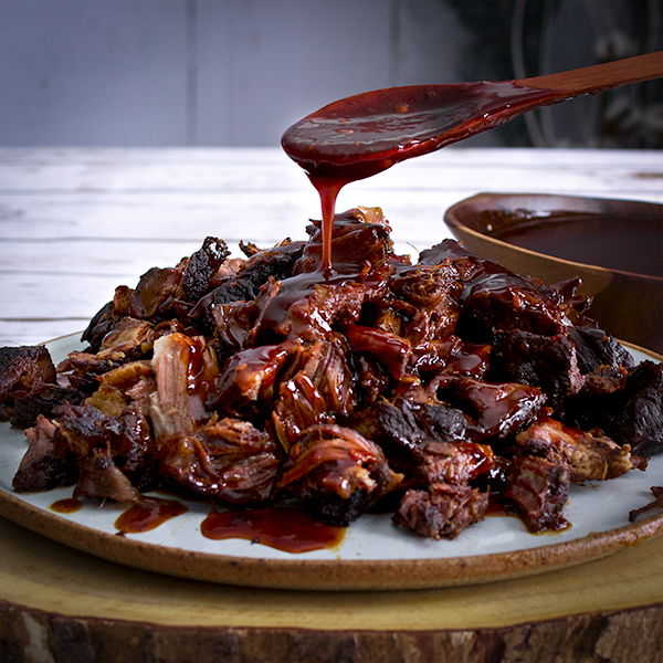 Pouring sauce over a plate of Asian Short Ribs.