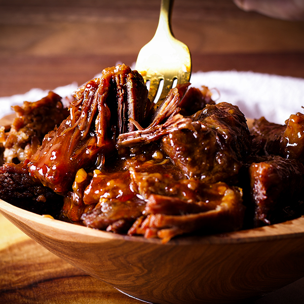 A bowl of Asian short rib meat with a fork, ready to eat.