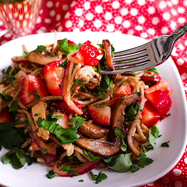 Taking a bite of Mushroom & Noodle Stir Fry with Strawberries & Chicken or tofu.