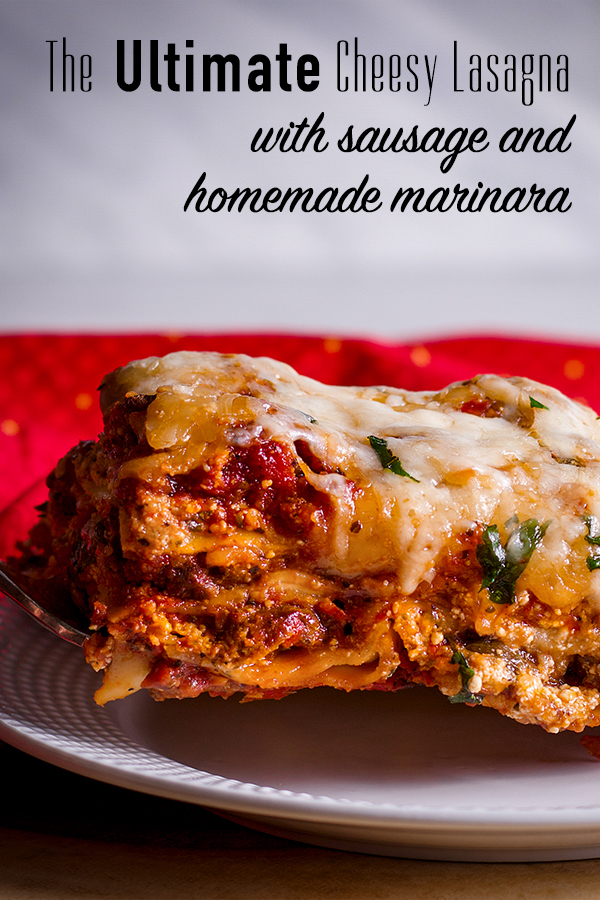 Using a spatula to set a slice of homemade lasagna with sausage on a plate.