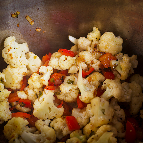 Sautéing cauliflower and other vegetables in a pan for Cauliflower and Chickpea Curry.