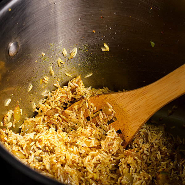 Stirring rice into Indian spices while cooking Indian Rice.