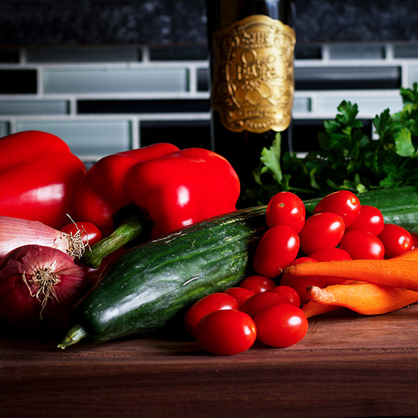 A cutting board with all the vegetables and ingredients for Israeli Salad.