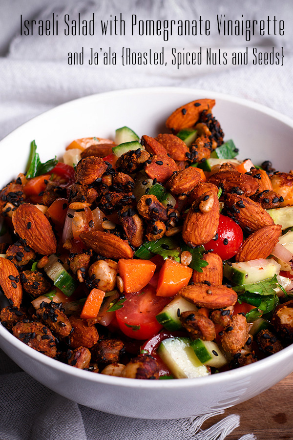 A bowl of Israeli Salad topped with roasted nuts and seeds.