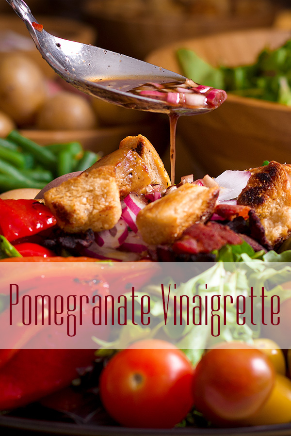 Drizzling pomegranate vinaigrette over a salad.