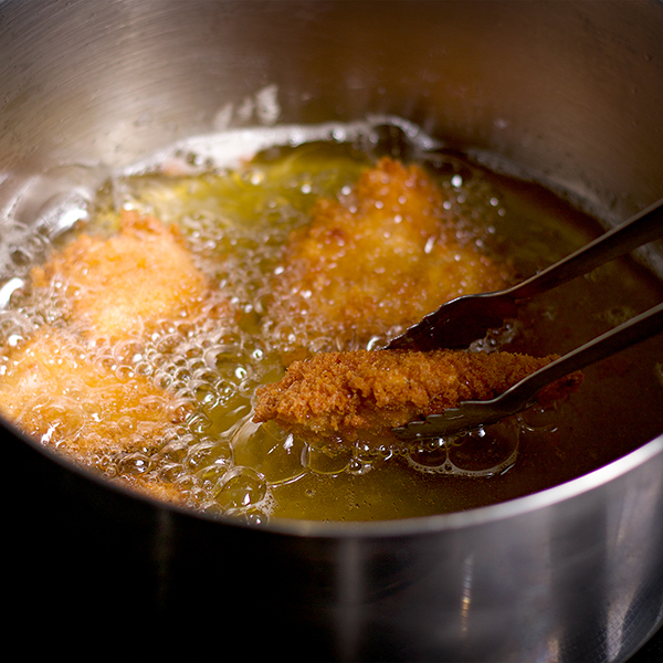 Frying pieces of chicken for Fried Chicken Pizza.