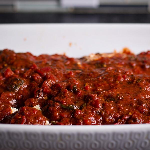 A pan of stuffed pasta shells covered in marinara sauce.