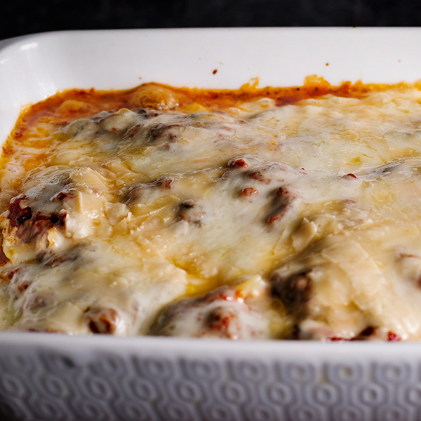 A pan of ricotta stuffed pasta shells that's been baked with marinara sauce and cheese and is ready to eat.