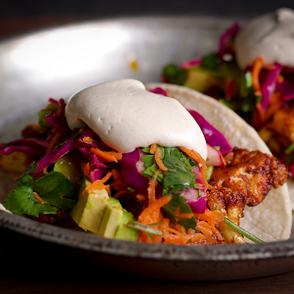 A plate with two Vegan Cauliflower Tacos with avocados, cabbage slaw, and vegan sour cream.